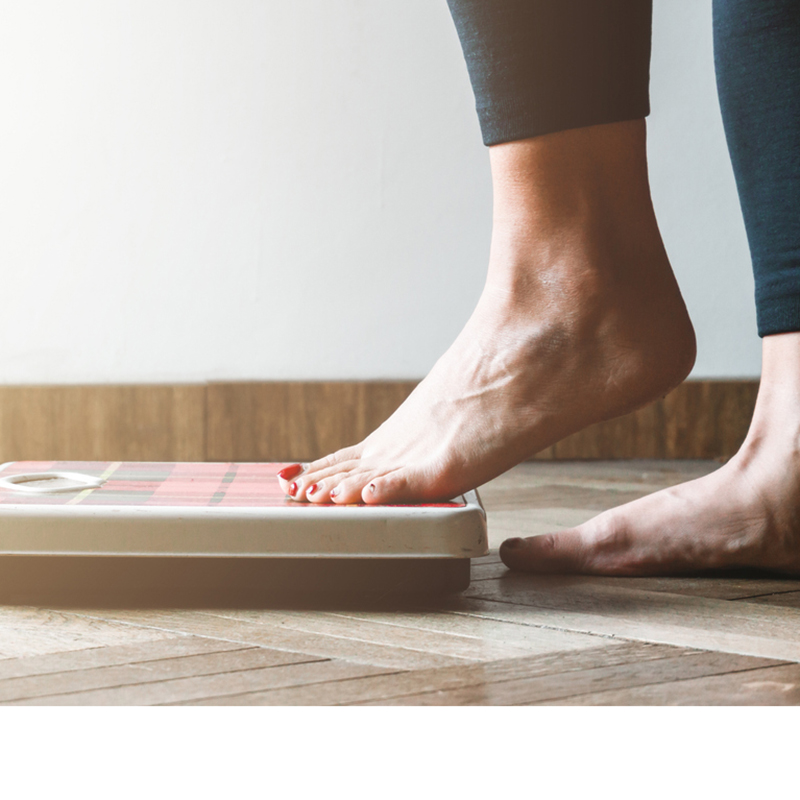 Close up of a woman stepping on the scales