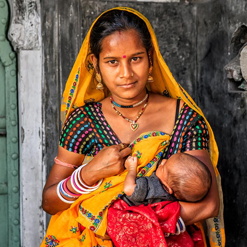 Indian woman in sari breastfeeding her baby
