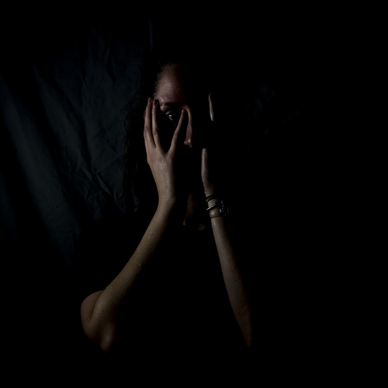 A woman covering her face in darkness
