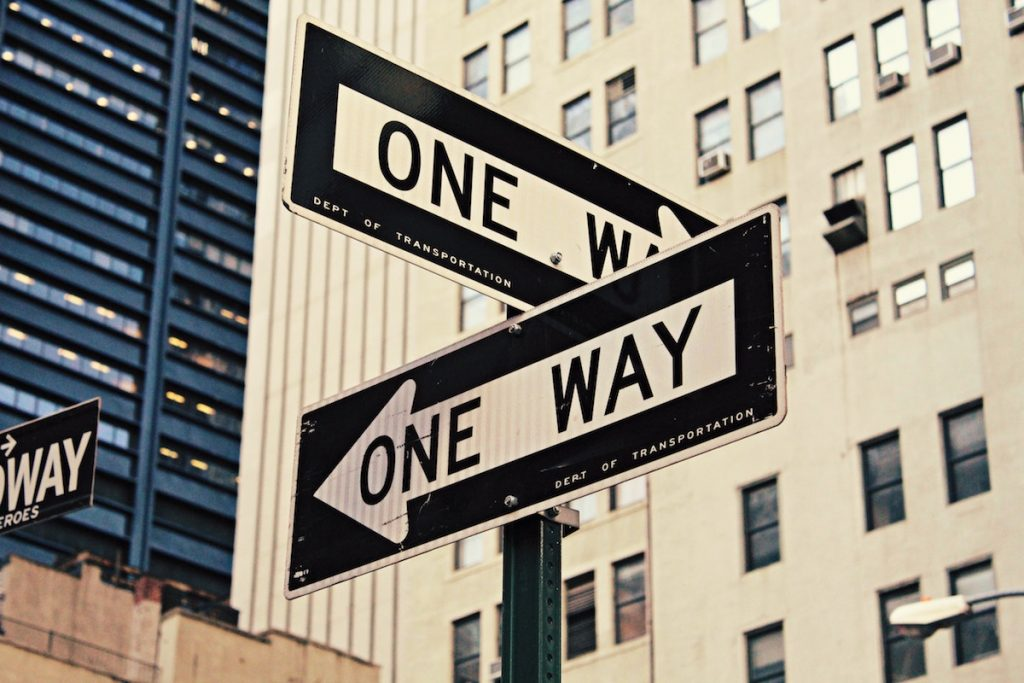 Two one way road signs pointing opposite directions