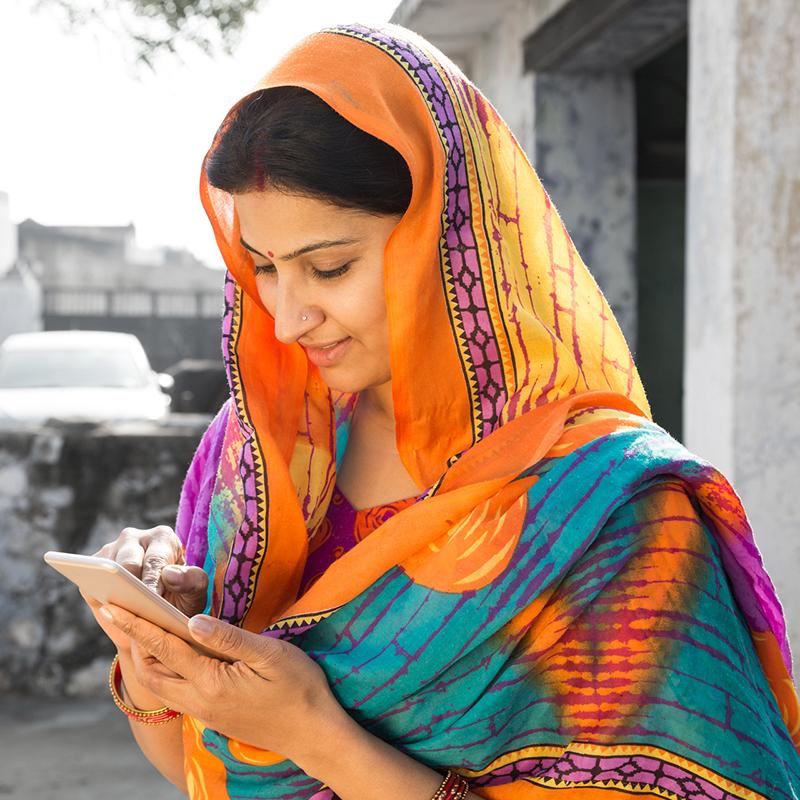 Smiling woman in sari browsing on her phone