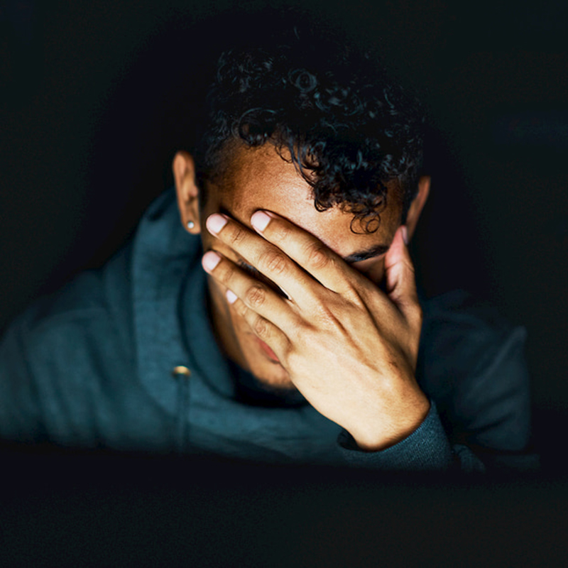 Worried stressed young man covering his face