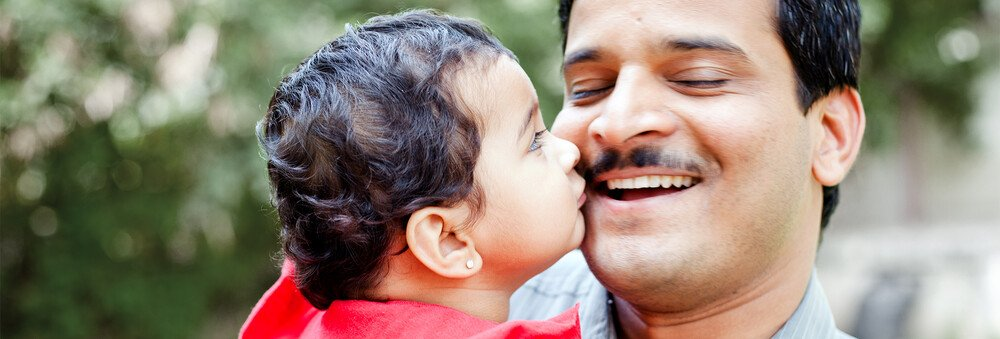 A child kissing his father